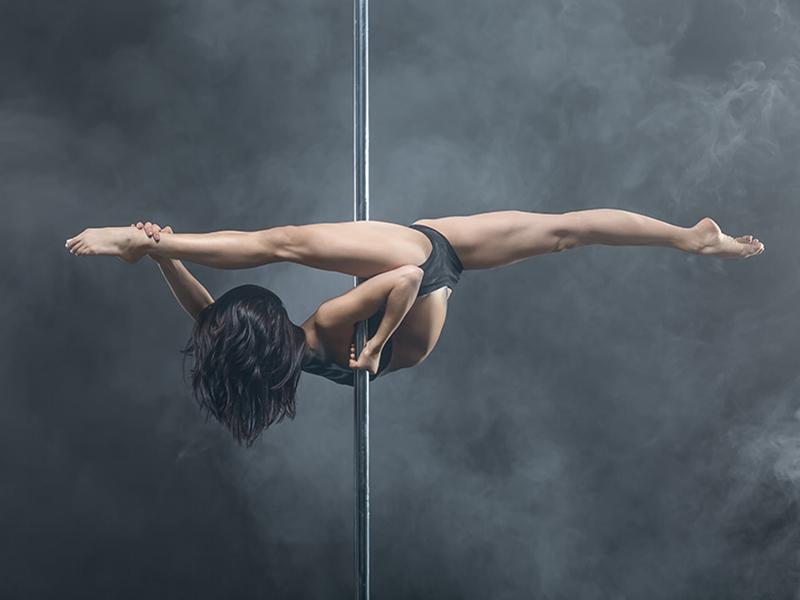 Female pole dancer posing in dark studio